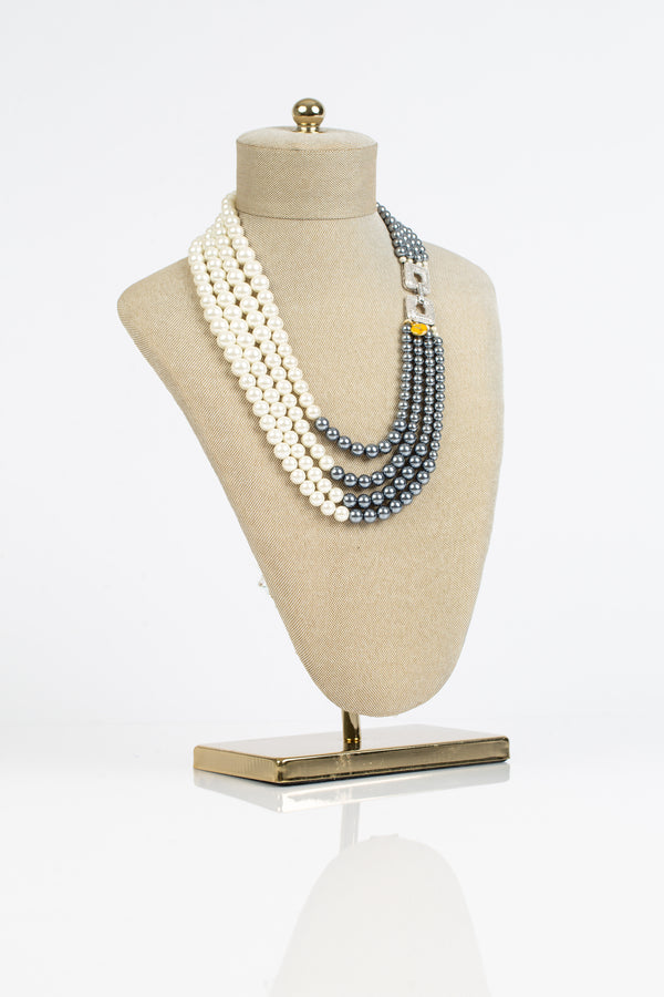 This necklace has four rows or grey and white pearls and is joined together with a crystal laden clasp.