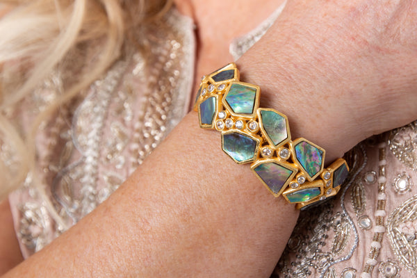 Asymmetrical natural Abalone stone is set in gold plated metal around Swarovski crystal to create this cuff that is easy to wear and fits most wrists.