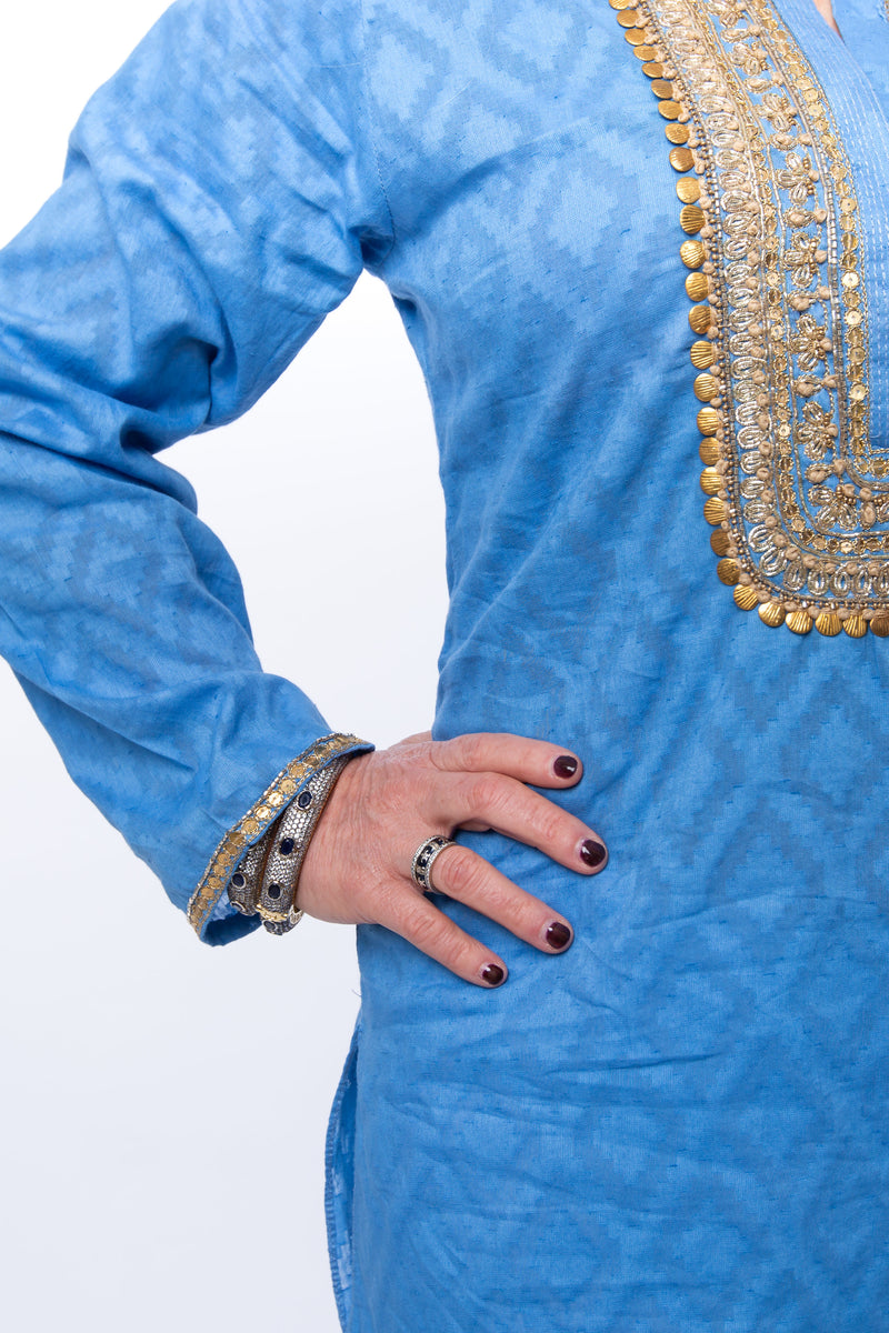 Hand woven blue tunic with intricate gold embroidery detail on sleeves, around the neck and on the back of the tunic.
