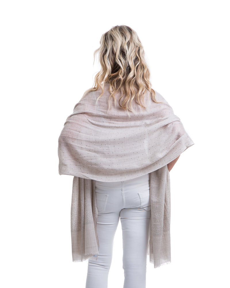 The Ethereal shawl is a hand woven light weight cashmere shawl that is embellished with gold Swarovski crystals over the entire length of the shawl. The shawl is sold in black or white.