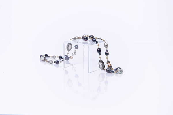 Natural black and grey baroque pearls encased in crystals. The necklace is 39 inches long with a toggle clasp. This necklace can be worn doubled or long. Hand crafted by artisans.