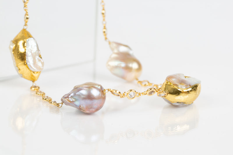 The Julia necklace showcases baroque pearls encase in gold plating on the edges and are strung together on a Swarovski laced chain. It is an all occasion necklace.