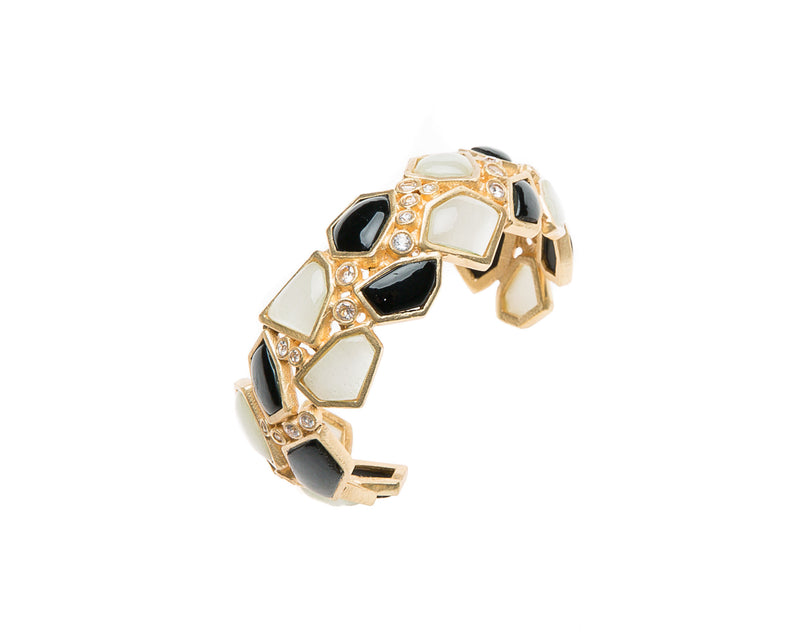 Asymmetrical natural black agate and mother of pearl are set in gold plated metal around Swarovski crystal to create this cuff that is easy to wear and fits most wrists.