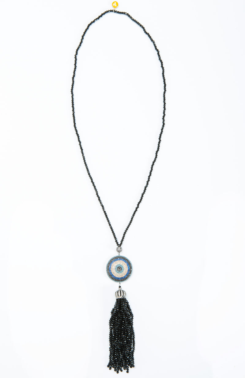 Classic evil eye dome tassel necklace with crystal and stone details. This necklace is worn long and is offered in shades of blue and black.