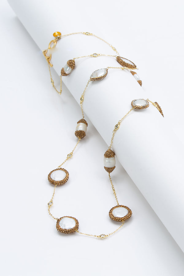 "The Elsa flat pearls necklace is 39 "" long. Each freshwater pearl is encrusted with Swarovski  crystals. A toggle clasp allows for the necklace to be worn long or doubled."