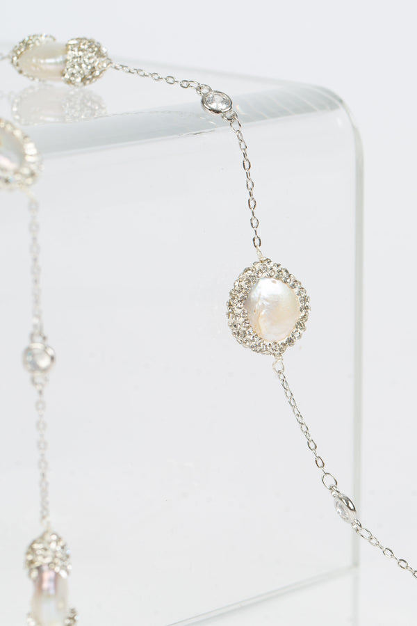"The Elsa flat pearls necklace is 39 "" long. Each freshwater pearl is encrusted with Swarovski  crystals. A toggle clasp allows for the necklace to be worn long or doubled. Image shows the necklace in white gold."