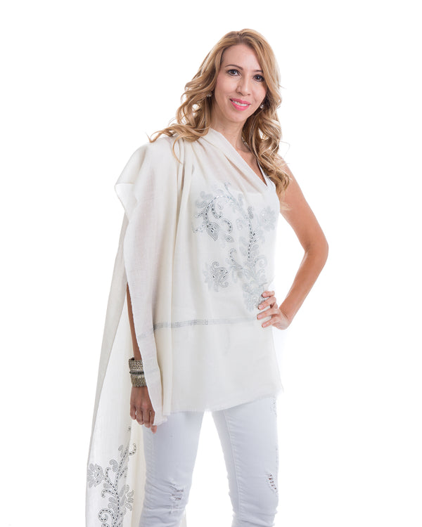 The image showcases the Yatra Halcyon Shawl that is offered in black and white. The cashmere shawl is decorated with large floral motifs at the two ends of the shawl with Swaravoski crystals in varied shapes and sizes.