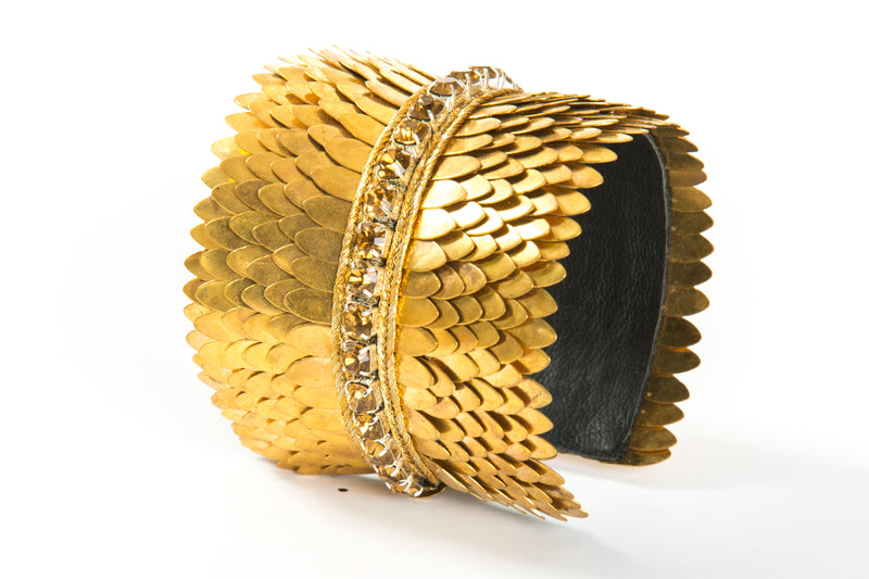 Wide gold plated cuff with feather cuts outs and a row of crystals in the center. The cuff is lined with soft leather for comfort. It is a significant piece that could be worn casually or to a black tie event.  It is offered in 3 finishes.