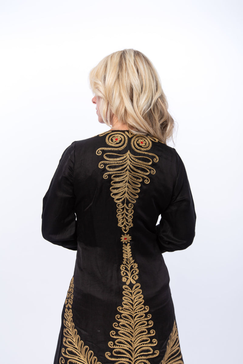 The image shows the Gwalior jacket. This is a highly embellished satin jacket that can be worn as a duster. The us extensive gold embroidery with red highlights on the back and sleeves of the of the jacket