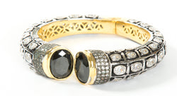 The images shows the Yatra.shop signature cuff. It is an easy to wear cuff with a hinge in the center. This cuff fits most wrists. It is embellished with enamel, Swarovski crystals of varying shapes and sizes and there are two round black semi precious stones at the opening.