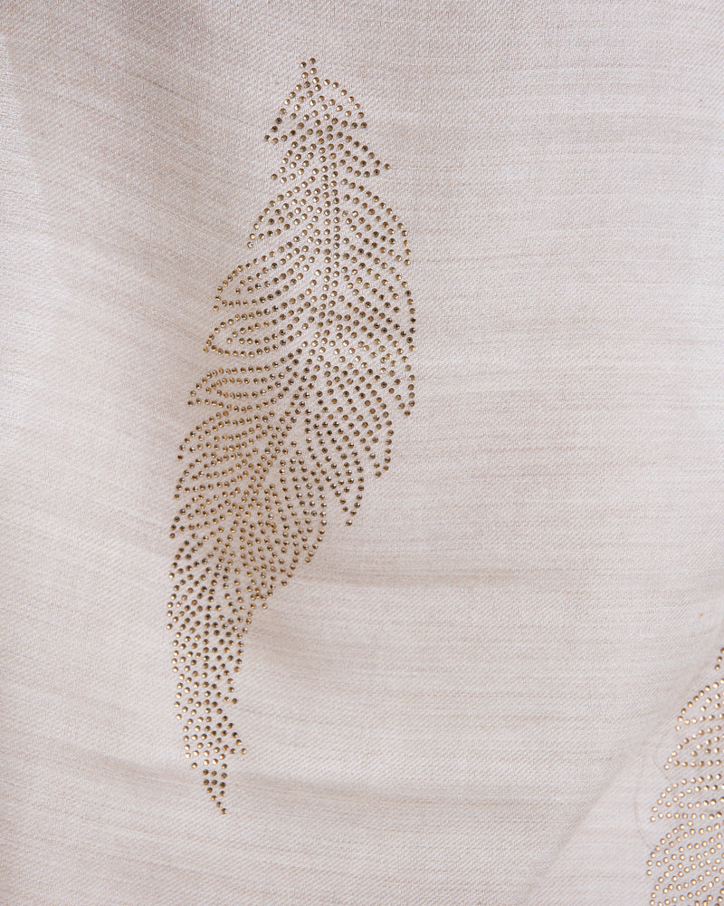 The Elixir cashmere shawl is embellished with Swarovski crystals. The crystals form a  leaf pattern all over the shawl. Two rows of crystals form a border along the two ends of the width.