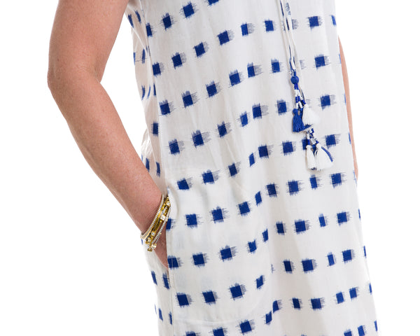 The Ikat dress is a sleeveless block printed dress that comes with a belt to define the waist. The dress is white with navy blue ikat block printing. The pockets add a nice finishing touch to the dress.