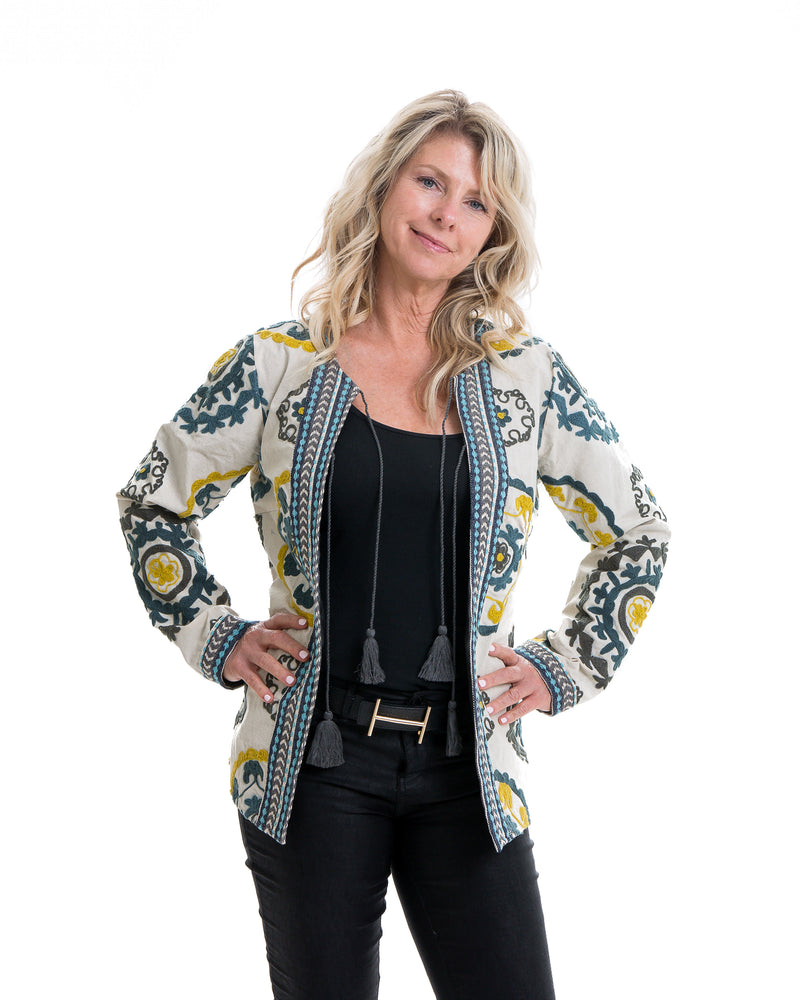 Hip length cotton jacket with extensive embroidery in various colors. The jacket is lined and has tassels enclosures.