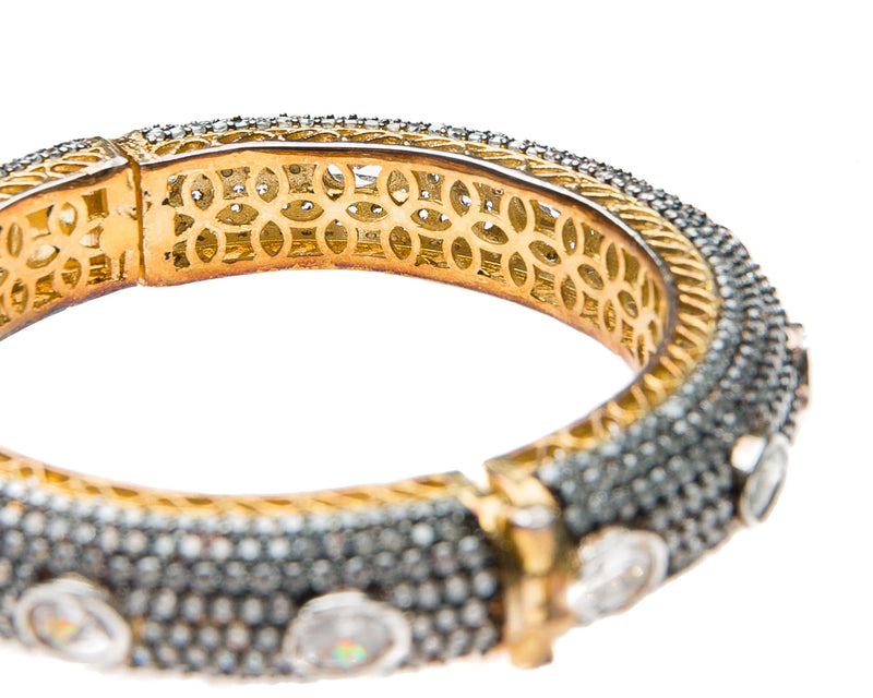 Hand-crafted bracelet with hinge in the center is easy to wear. The cuff is covered in Swarovski crystals of varying sizes. There is delicate filigree detail on the inside of the bracelet. The bracelet is 18k gold plated.