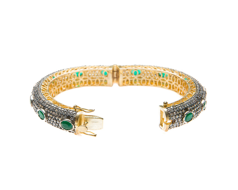 Hand-crafted bracelet with hinge in the center is easy to wear. The cuff is covered in clear Swarovski crystals. Semi precious green oval stones are spaced in intervals along the cuff.There is delicate filigree detail on the inside of the bracelet. The bracelet is 18k gold plated.