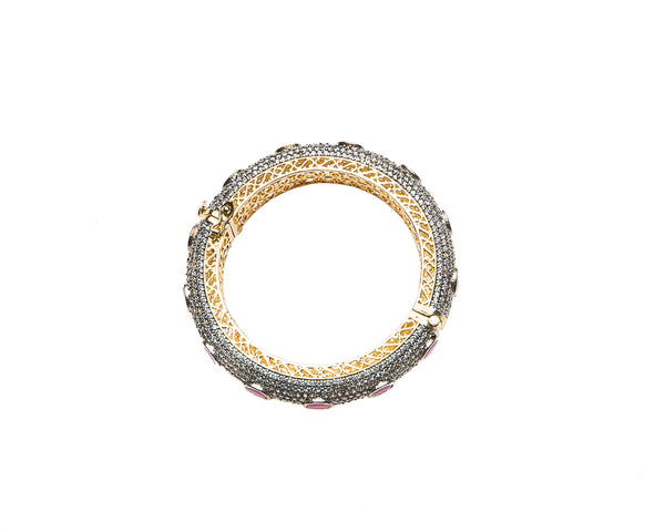 Hand-crafted bracelet with hinge in the center is easy to wear. The cuff is covered in clear Swarovski crystals. Semi precious red oval stones are spaced in intervals along the cuff.There is delicate filigree detail on the inside of the bracelet. The bracelet is 18k gold plated.