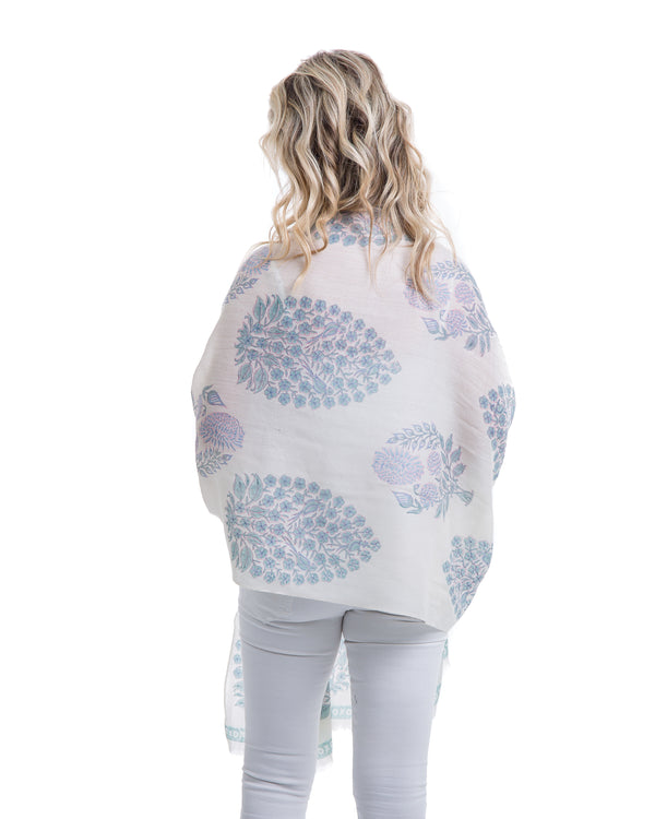 The Islamorada Shawl is a block printed shawl. The base of the shawl is white with bold floral block pints in shades of blue.