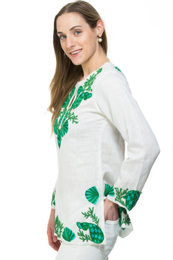 White linen tunic with substantial hand embroidery with faux coral detail. The embroidery is in either green, red or blue. Embroidery detail in around the neck, sleeves and at the bottom of the tunic.