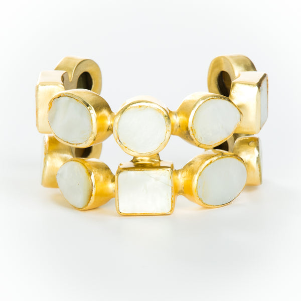 Two rows of natural white mother-of-pearl set in brass and 18k electro-gold plated. Adjusts to fit most wrists.