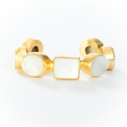 Natural white mother-of-pearl stones set in brass and 18k electro-gold plated. Adjusts to fit most wrists.