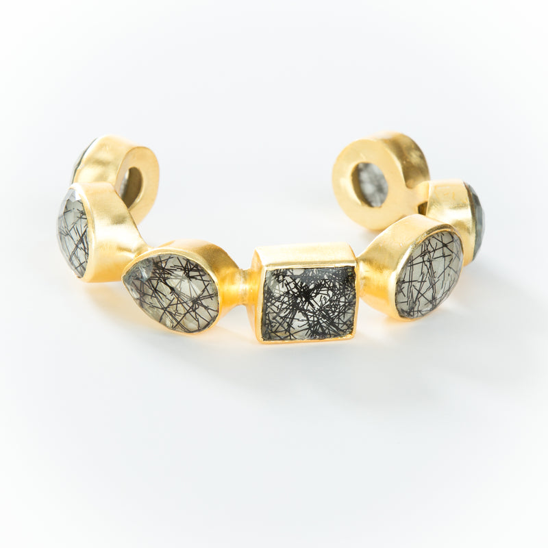 Natural black rutilated quartz stones set in brass and 18k electro-gold plated. Adjusts to fit most wrists.