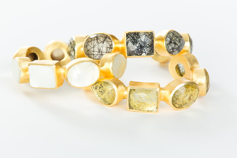 Natural yellow rutilated quartz set in brass and 18k electro-gold plated. Adjusts to fit most wrists.