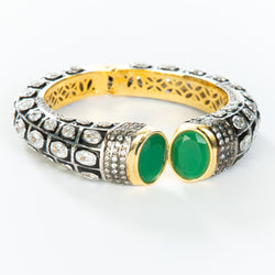 The images shows the Yatra.shop signature cuff. It is an easy to wear cuff with a hinge in the center. This cuff fits most wrists. It is embellished with enamel, Swarovski crystals of varying shapes and sizes and there are two round green semi precious stones at the opening.