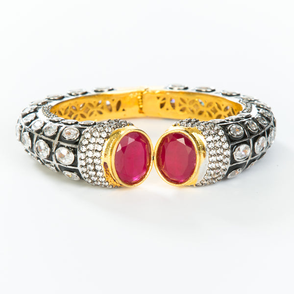 The images shows the Yatra.shop signature cuff. It is an easy to wear cuff with a hinge in the center. This cuff fits most wrists. It is embellished with enamel, Swarovski crystals of varying shapes and sizes and there are two round red semi precious stones at the opening.