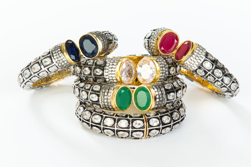 The images shows the Yatra.shop signature cuff. It is an easy to wear cuff with a hinge in the center. This cuff fits most wrists. It is embellished with enamel, Swarovski crystals of varying shapes and sizes and there are two round clear semi precious stones at the opening.