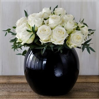 White avalanche roses with foliage in a black goldfish bowl vase