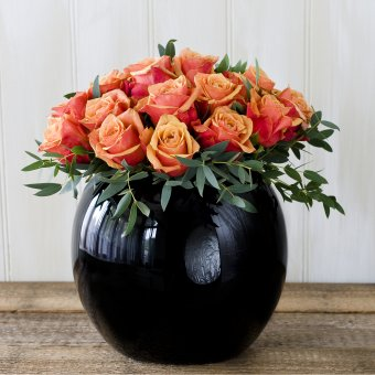 Cherry brandy orange roses and foliage in a black goldfish bowl vase