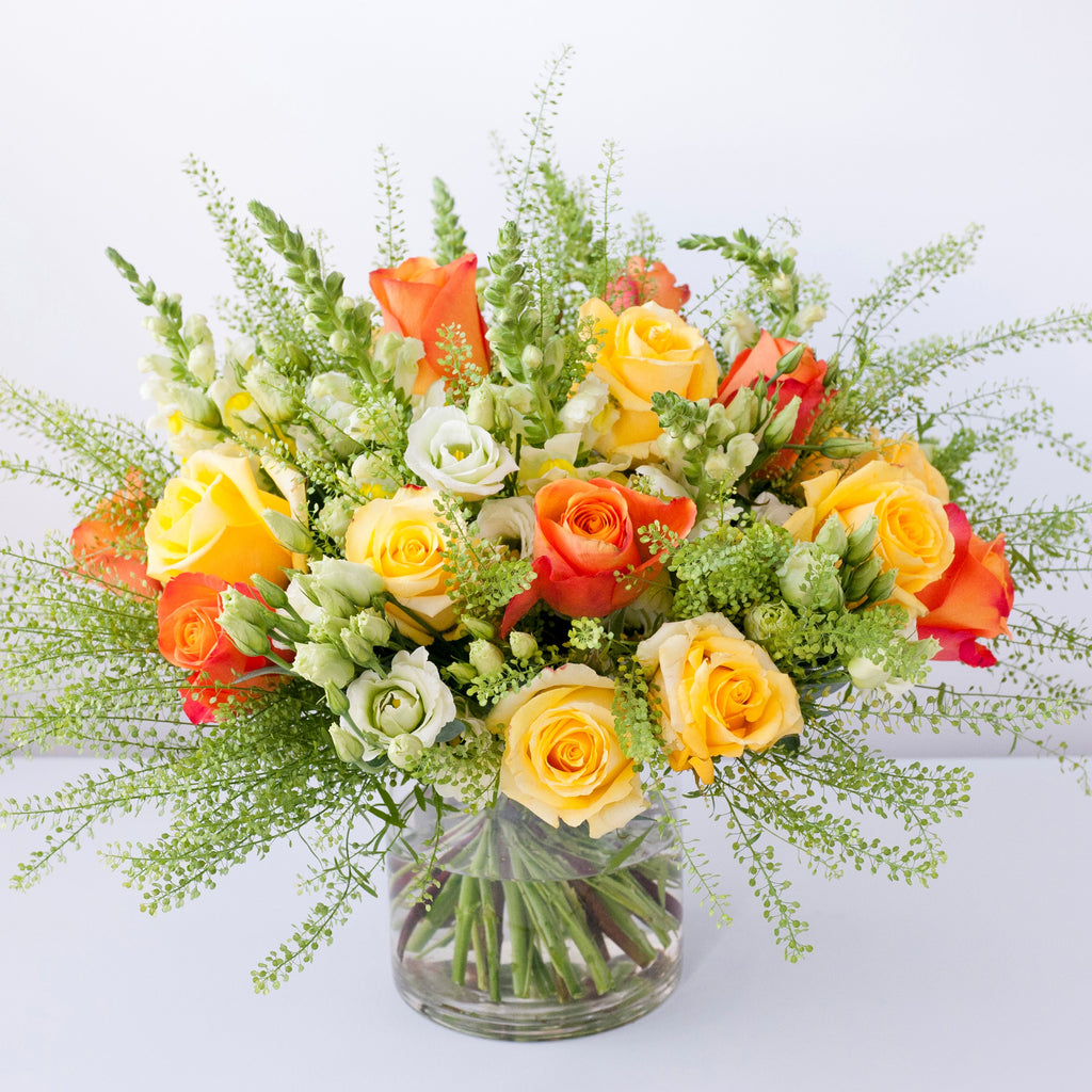 Image of yellow roses, white antirrhinum, green lisianthus, orange roses and foliage in a vase