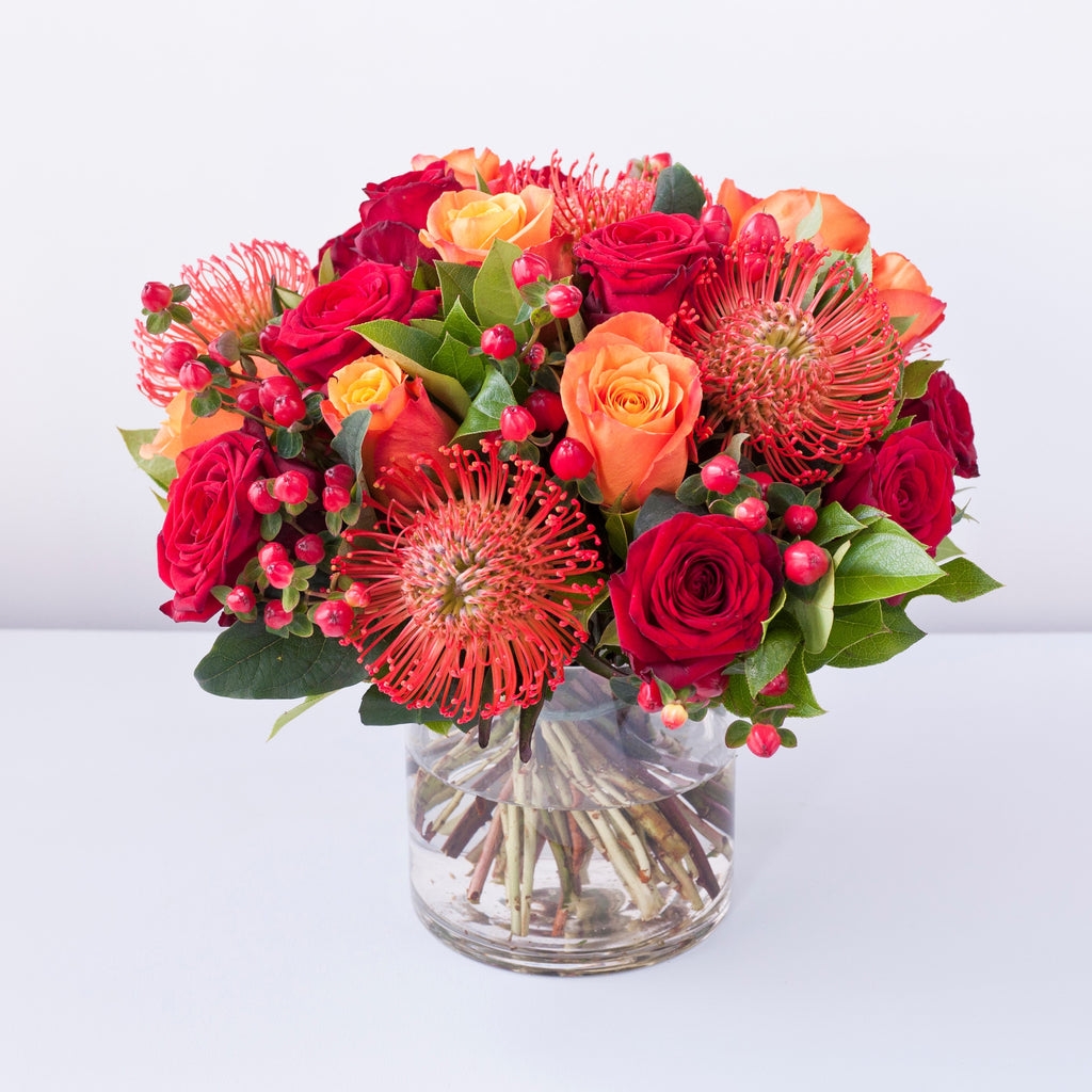Grand prix red roses, cherry brandy orange roses, red proteas, hypericum berries and foliage