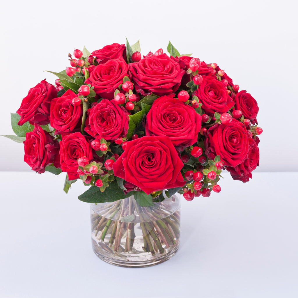 Grand prix red roses with hypericum berries and foliage in a vase