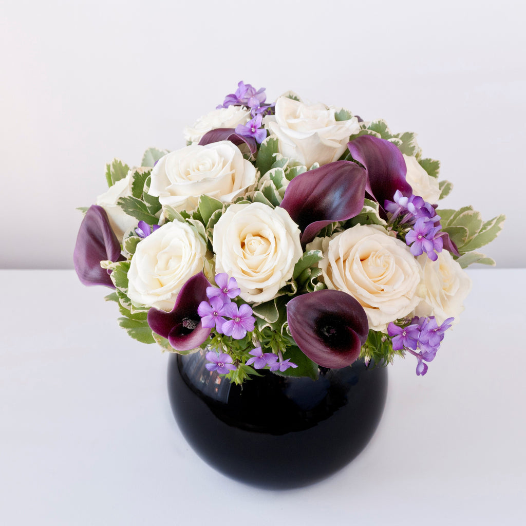 Image of white roses, burgundy calla lilies, purple phlox and foliage in a black goldfish bowl vase