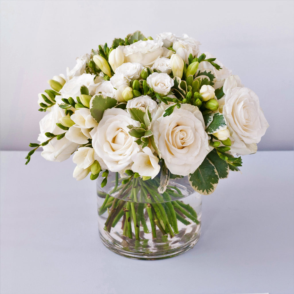 Image of white avalanche roses, white freesias, white spray roses and folisge