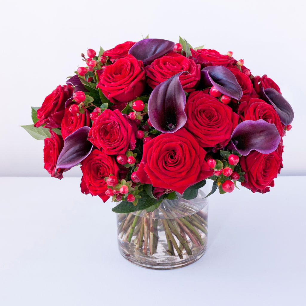 Red roses, wine coloured calla lilies, red hypericum berries in a clear vase