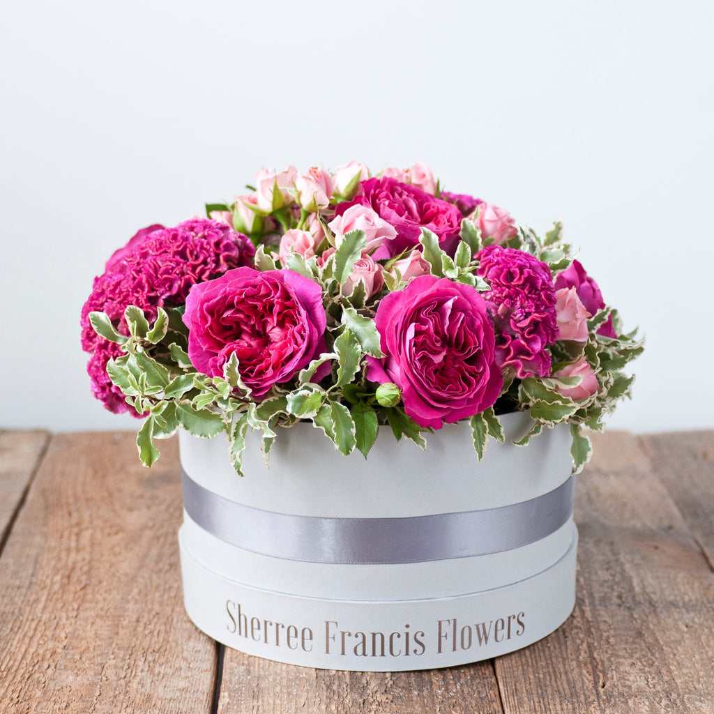Image of hat box filled with cerise pink piano rises, pink celosia, pink spray roses and foliage