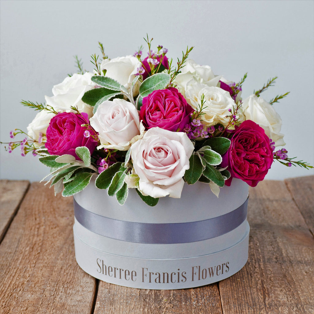 Hat box filled with cerise pink and light pink roses and foliage