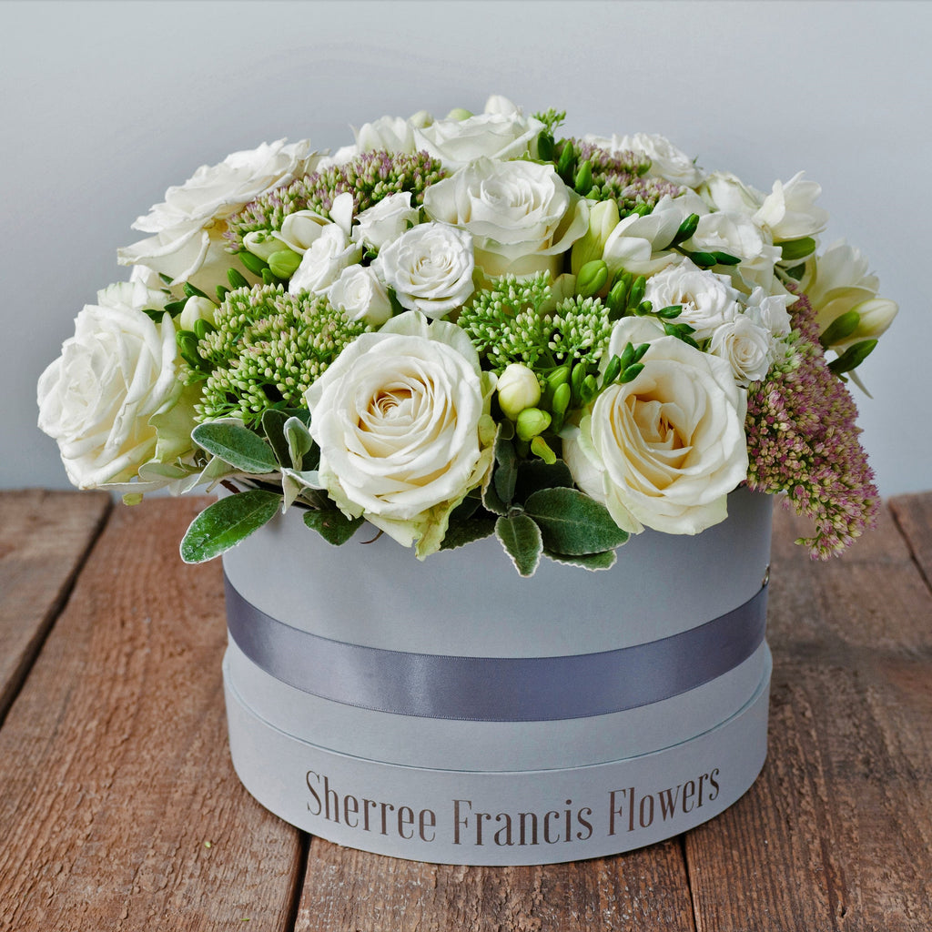 Hat box filled with white Avalanche roses, white spray roses, freesias, sedum and foliage