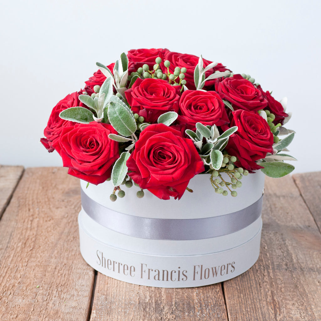 Image of grey hat box filled with red roses and foliage
