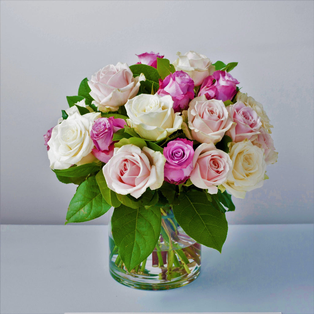 Pale pink, lilac and white roses with foliage in a vase
