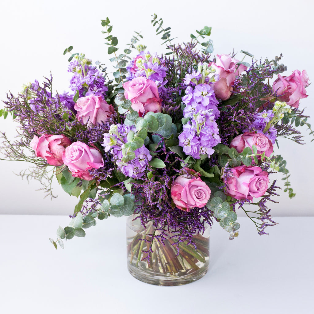 Image of vase of flowers with purple lisianthus, memory lane pink roses, lilac stocks, lilac freesias, with purple statice and foliage.