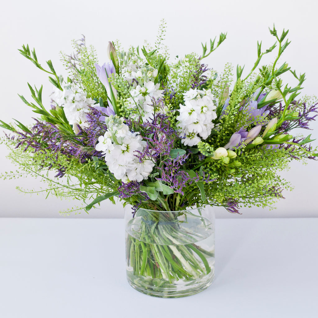 Image of lilac freesias, white stock, purple statice, foliage in a vase