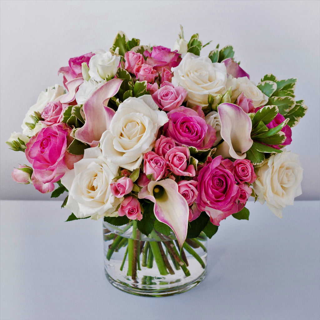 Bubblegum pink roses, white avalanche roses, white lisianthus, pale pink calla lilies in a vase