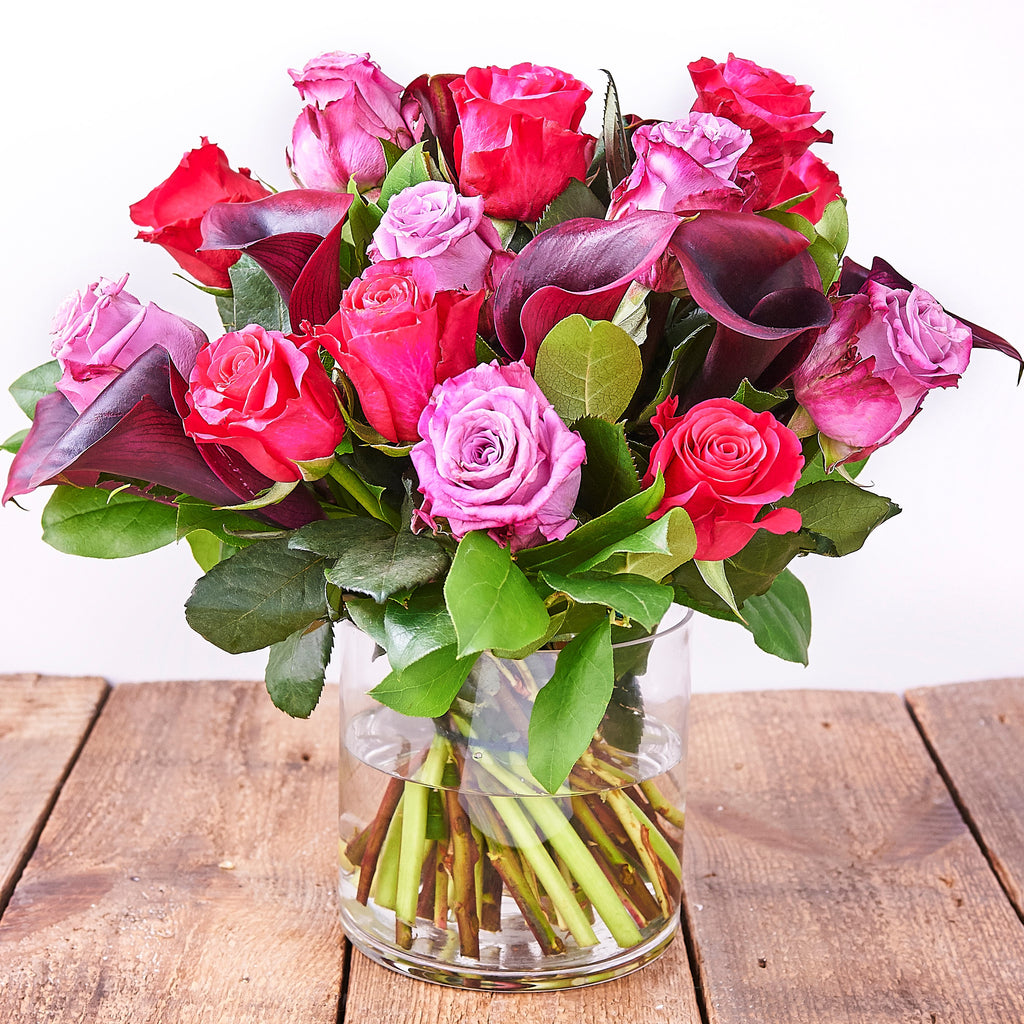 Cerise pink Milano roses, pale pink Revival roses, antique pink Memory Lane roses and aubergine calla lilies and seasonal foliage