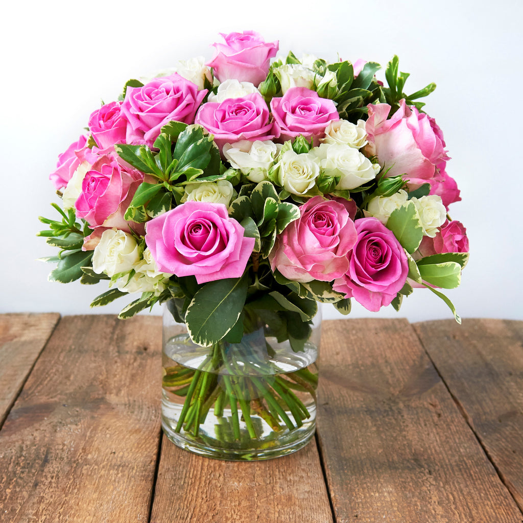 Vase of bubble gum pink roses and white spray roses and foliage.