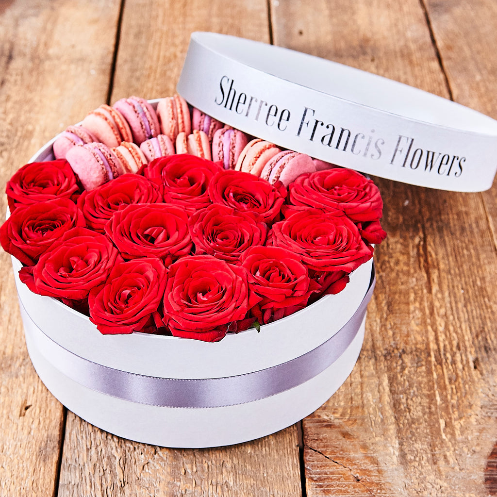 Hat box filled with red roses and macaroons