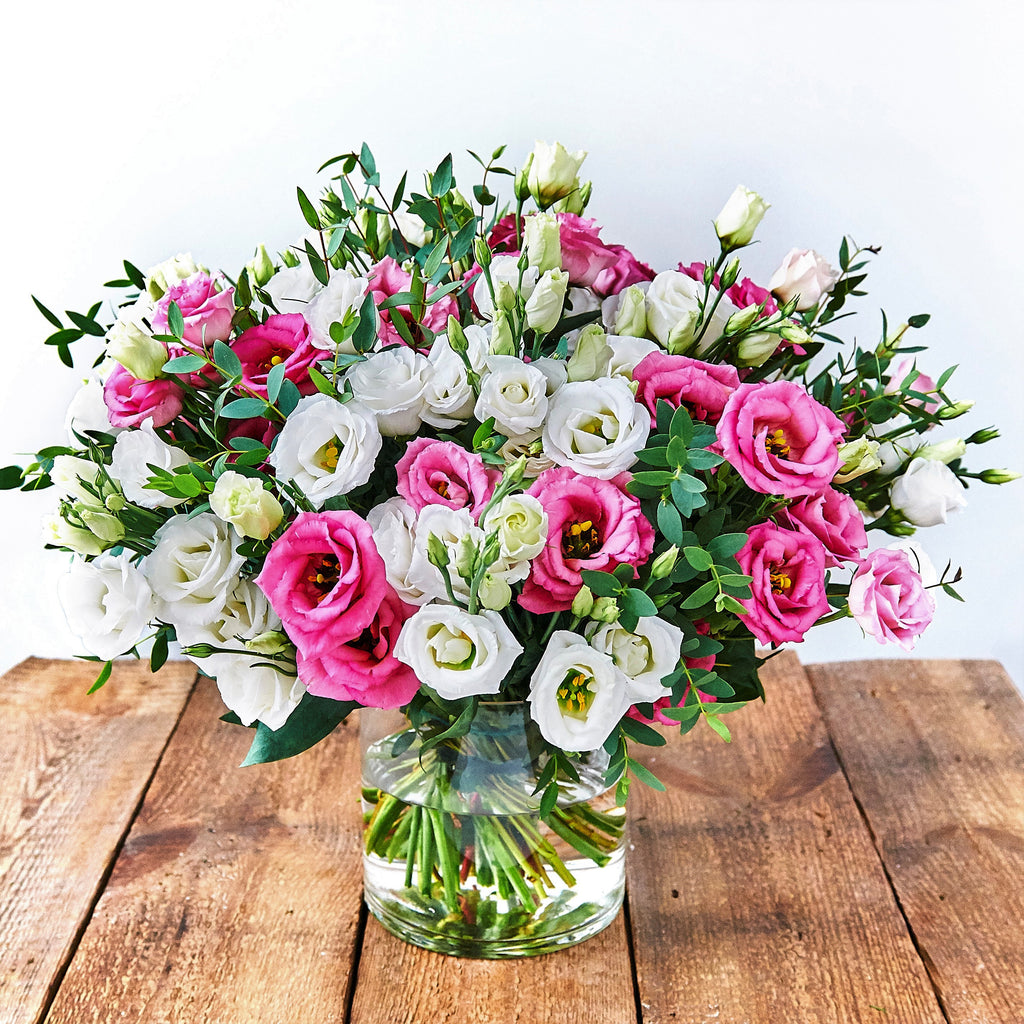 Vase of white and pink lisianthus stems