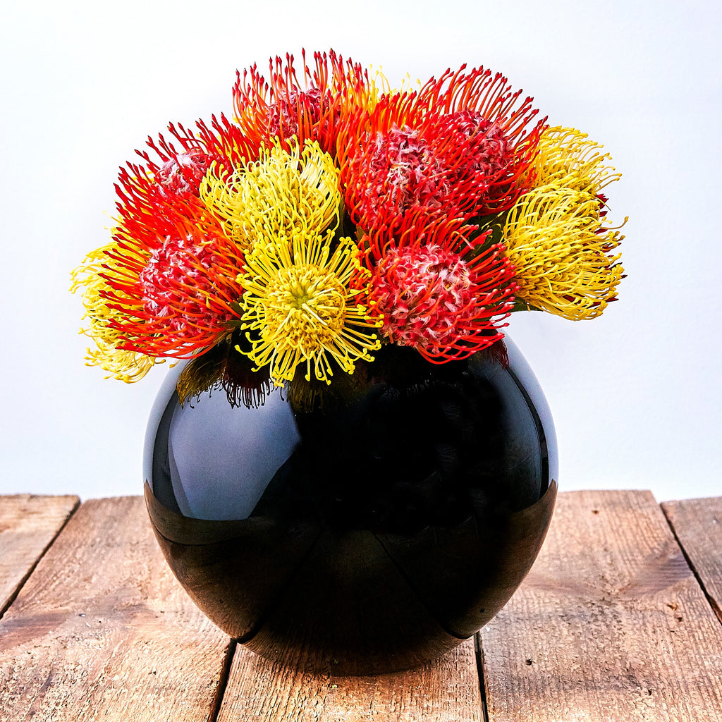 Black goldfish vase with red and yellow proteas